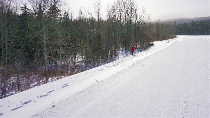 Kvinnasnöskor längs den snöig vägrenen i Vermont royaltyfri bild