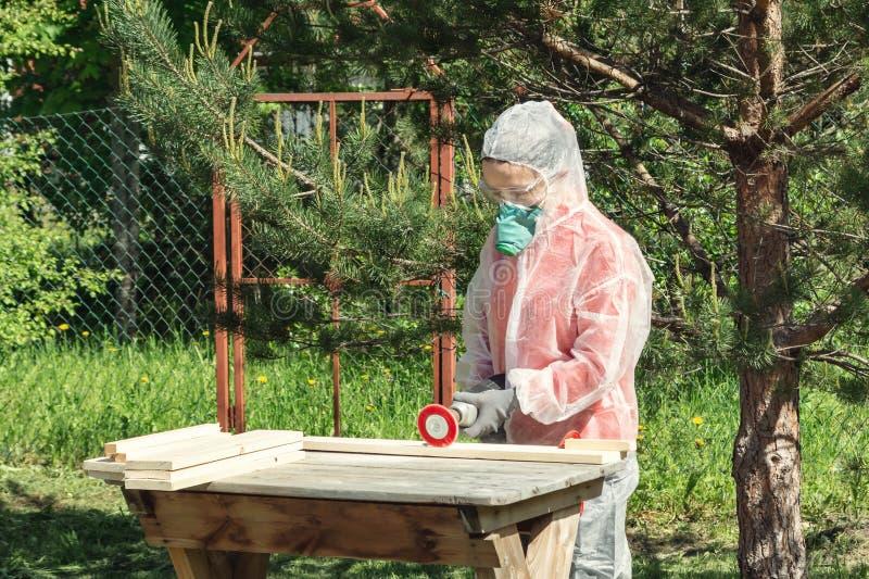 Kvinnasnickaren i respirator, skyddsglasögon och overaller behandlar ett träbräde med en vinkelmolar arkivfoton