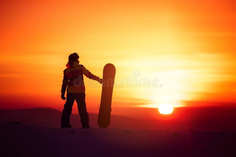 Kvinnasnowboarderkontur på solnedgångbakgrunden arkivfoton