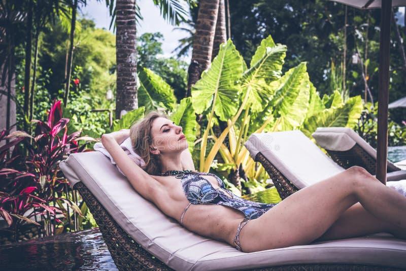 Kvinnasommarmode Lycklig sexig flicka med passformkroppen, långa ben, sund hud i bikinin som solbadar vid simbassängen på arkivfoton