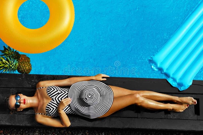 Kvinnasommarmode Sexig flicka som solbadar vid simbassängen _ arkivbild