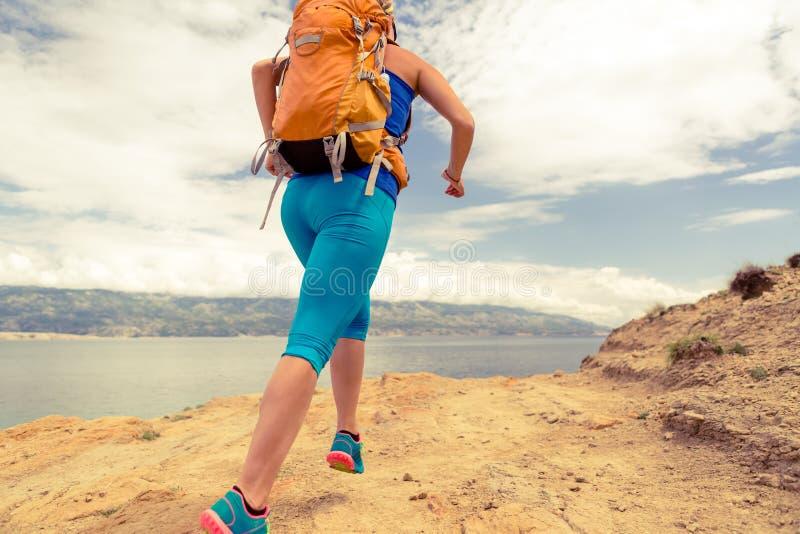 Kvinnaspring med ryggsäcken på stenig slinga på sjösidan royaltyfri fotografi