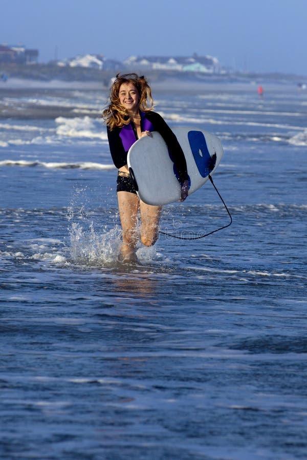 Kvinnaspring med surfingbrädan arkivbilder