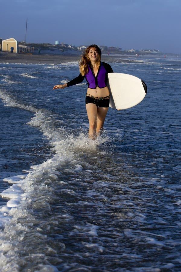 Kvinnaspring med surfingbrädan royaltyfria foton