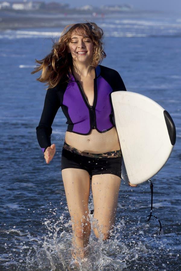 Kvinnaspring med surfingbrädan arkivbild