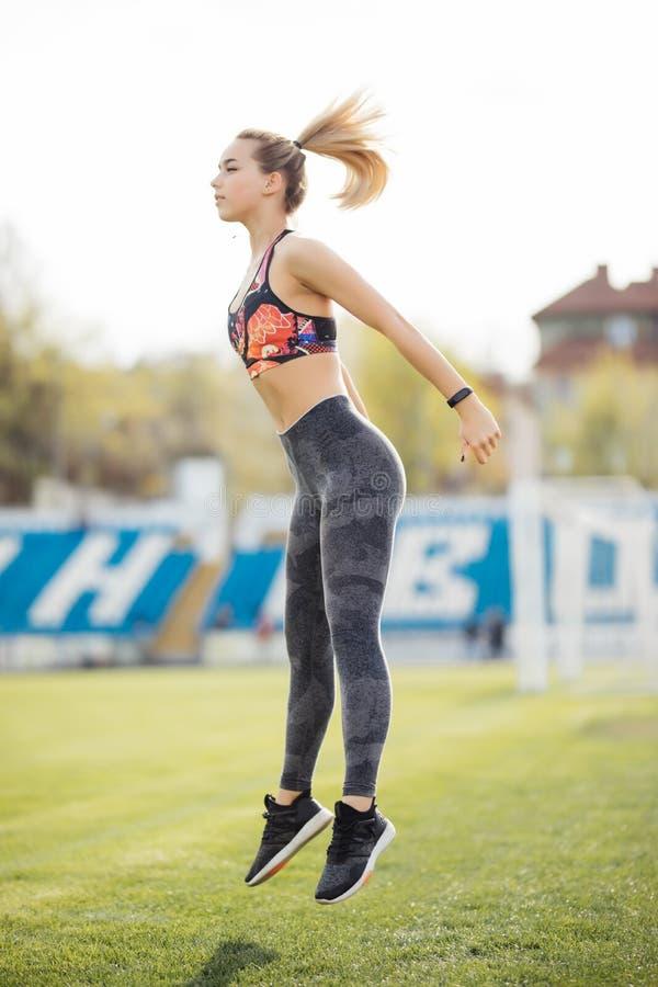 Kvinnaspring och banhoppning för kondition sportig i parkera royaltyfri foto