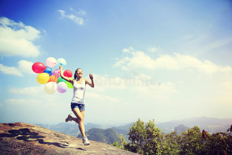 Kvinnaspring på bergmaximum vaggar med kulöra ballonger royaltyfri fotografi