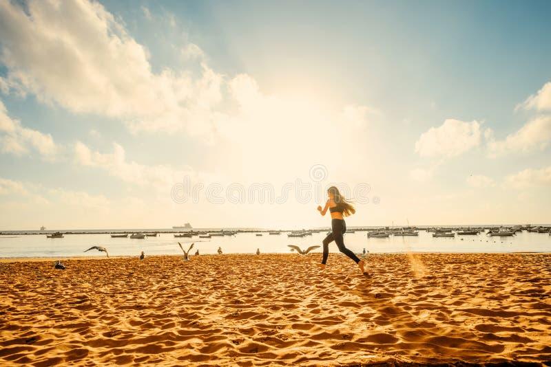 Kvinnaspring på den sandiga stranden arkivbild