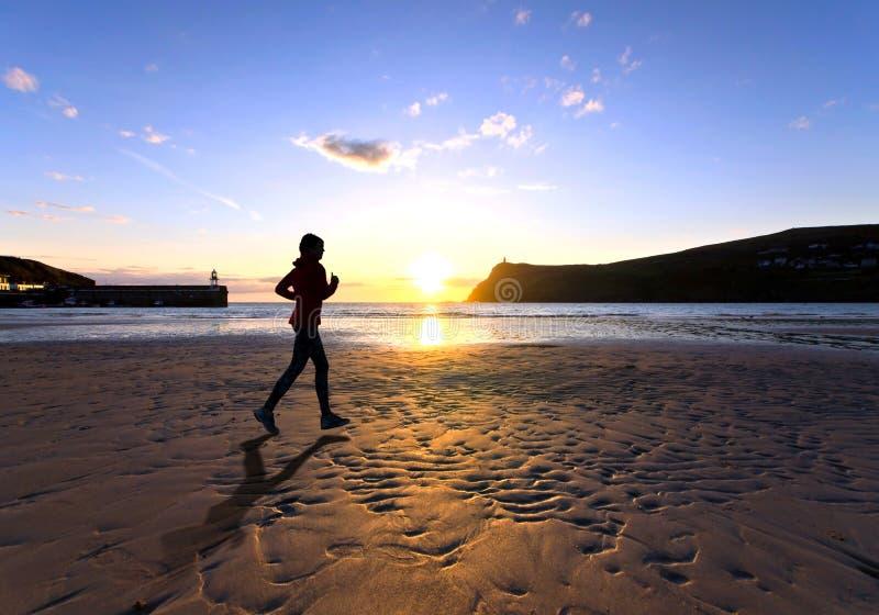Kvinnaspring på en strand under solnedgång royaltyfria bilder