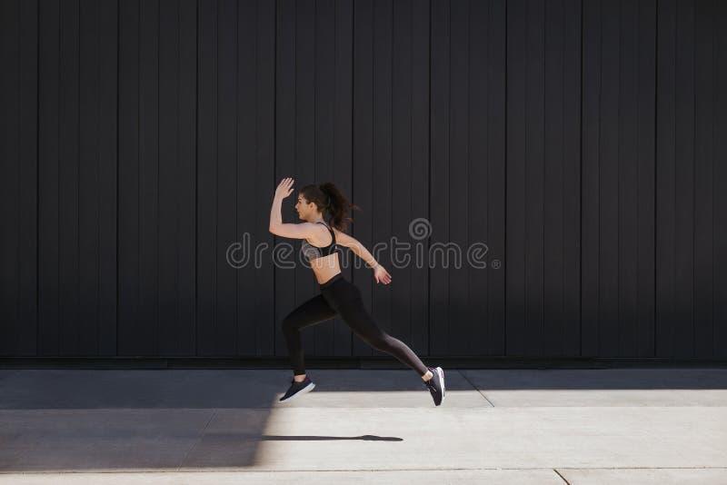 Kvinnaspring på stadsgatan mot moderna stadsväggar royaltyfri bild