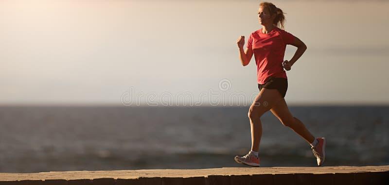 Kvinnaspring på stranden i morgonsoluppgång royaltyfri fotografi