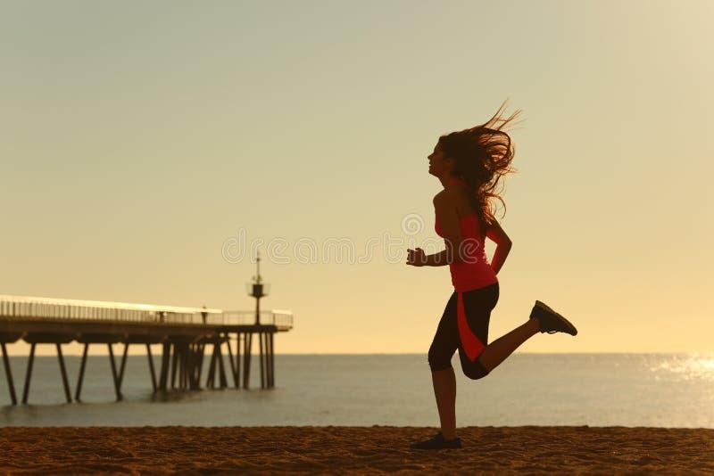 Kvinnaspring på stranden på soluppgång royaltyfri bild