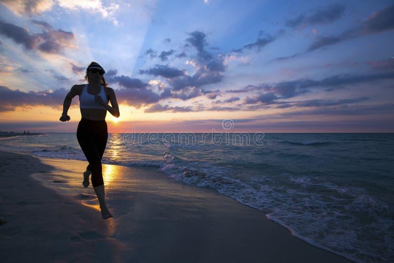 Kvinnaspring på stranden under solnedgång arkivfoto