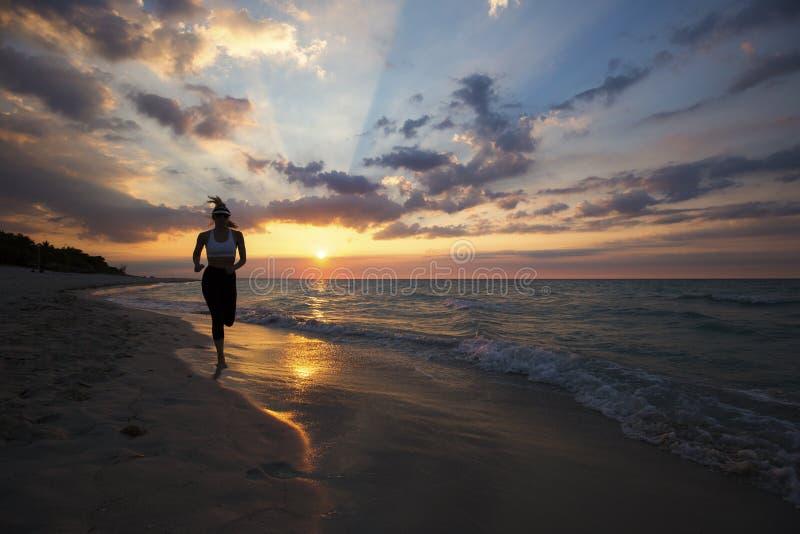 Kvinnaspring på stranden under solnedgång fotografering för bildbyråer