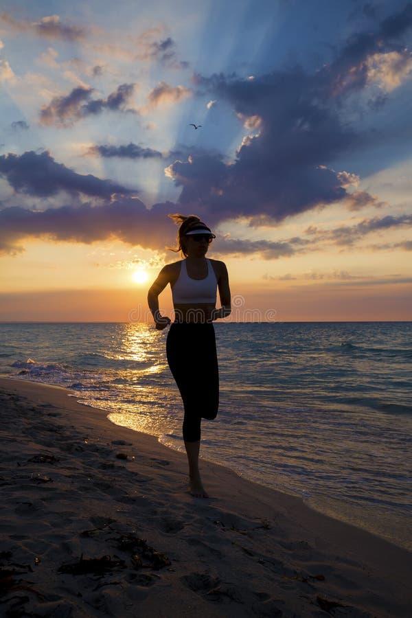 Kvinnaspring på stranden under solnedgång royaltyfria bilder