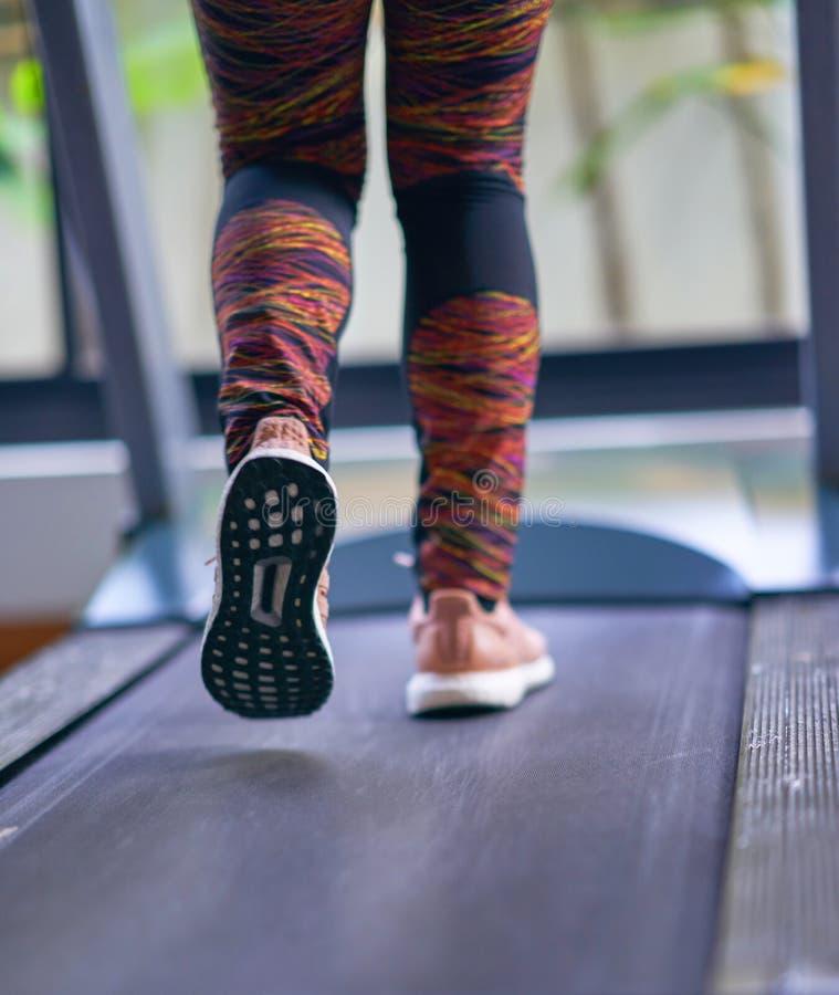 Kvinnaspring på trampkvarnen i konditionidrottshallen med sportskor, baksida royaltyfria bilder