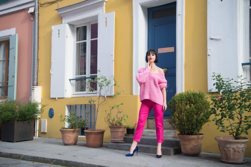 Kvinnaställning i skor för hög häl i paris, Frankrike, semester Kvinna i den rosa tröjan, byxa på gatan, mode Skönhet blick, make royaltyfri foto