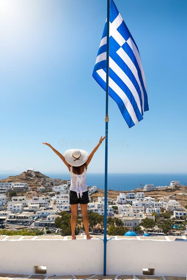 Kvinnaställningar bredvid en stor grekisk flagga och tycker om sikten över ön av Ios arkivfoto