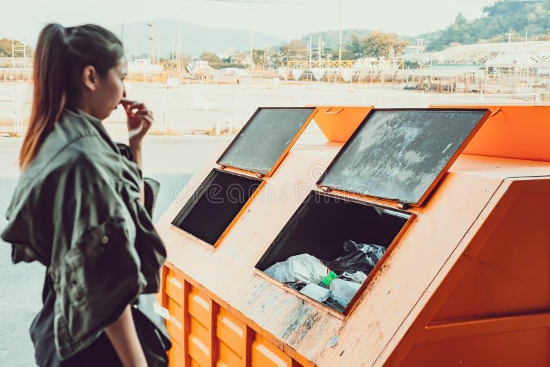 Kvinnaställningen nära avfall och hon luktar att stinka smutsigt avfall royaltyfri foto