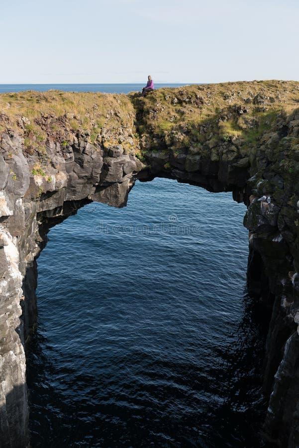 Kvinnaställningen på ett naturligt stenar porten vid havet Svart vulkaniskt vaggar klippan av den västra isländska kustSnaefellsn arkivbilder