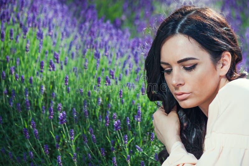 Kvinnastående för mörkt hår som är utomhus- i lavendel fotografering för bildbyråer