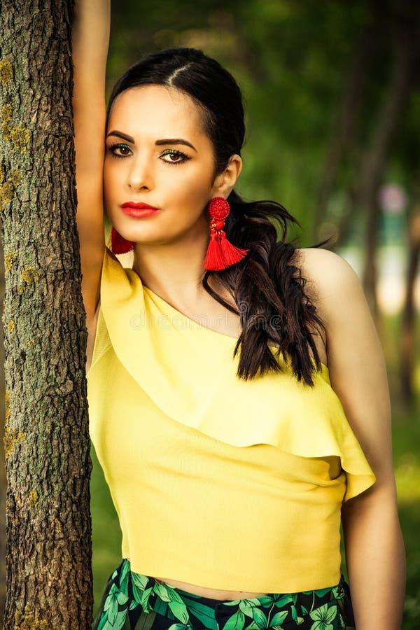 Kvinnastående för mörkt hår vid trädlatinoblicken royaltyfri fotografi