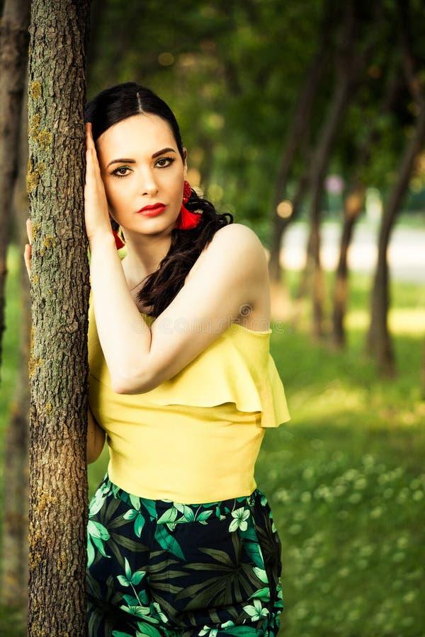 Kvinnastående för mörkt hår vid trädlatinoblicken royaltyfria foton