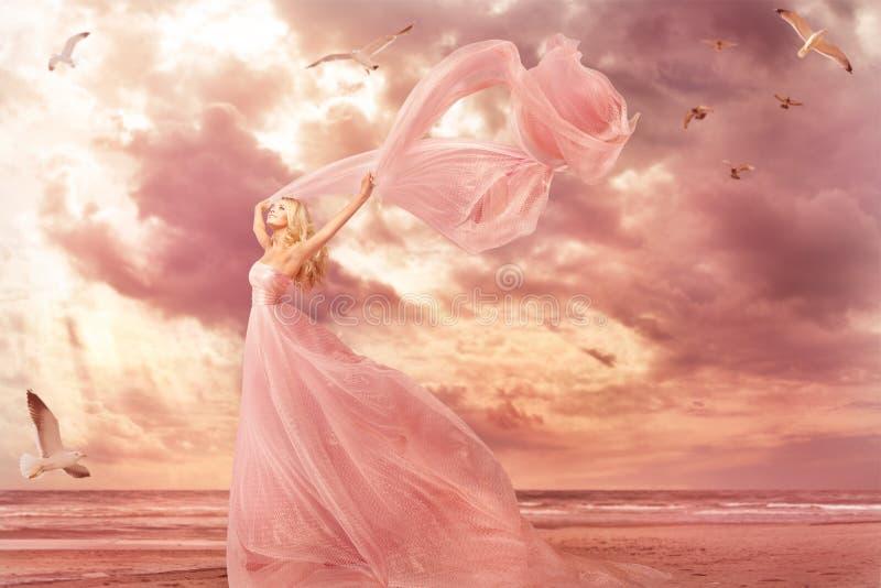Kvinnastående i lång klänning på havskusten, kappa för fantasiflickarosa färger i stormvind royaltyfri foto