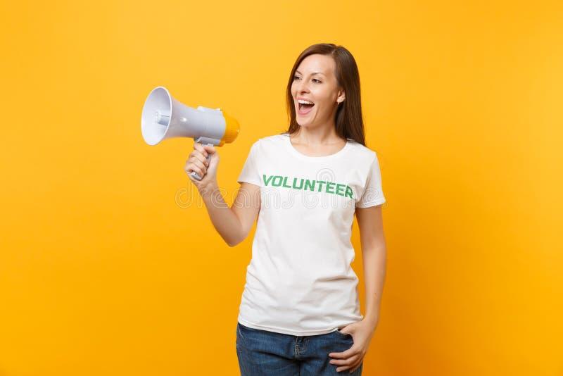 Kvinnastående i megafonen för adress för skri för volontär för titel för vit t-skjorta den skriftliga inskriftgräsplan som offent royaltyfri fotografi
