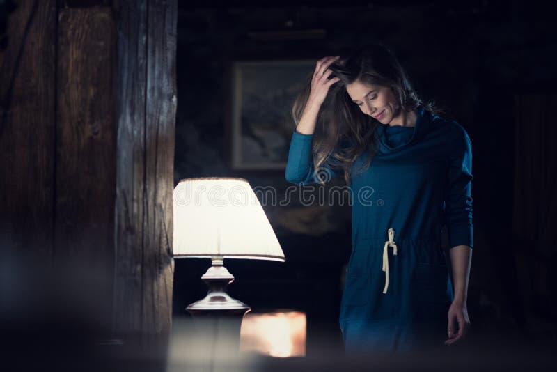 Kvinnastående som bär den tillfälliga klänningen som ler och ser ner den near lampan den vardagsrum på lantligt hem- inomhus Euro arkivbild