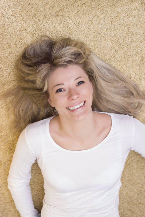 Kvinnastående som ligger på golvet och le arkivfoto