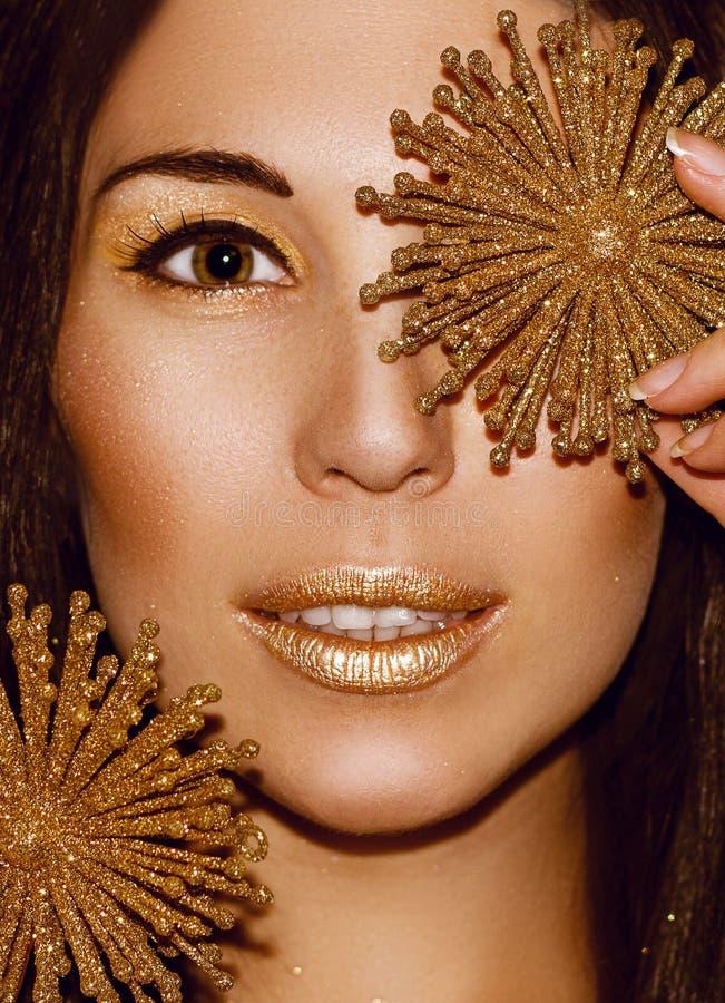 Kvinnaståendebrunett med julpyntguldsnöflingor royaltyfri bild