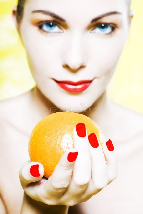 Kvinnaståendeerbjudande orange le arkivfoto