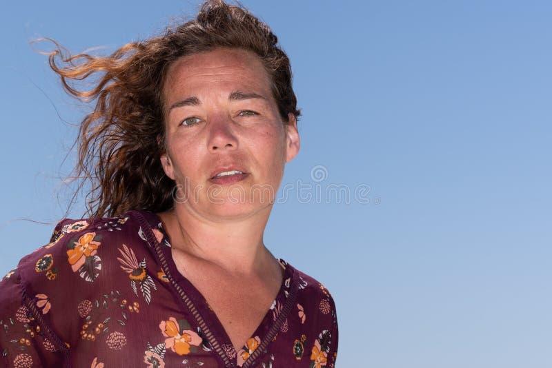 Kvinnaståendevind i hår mot klar blå himmel arkivfoton