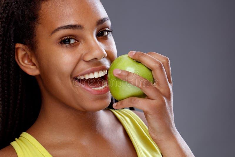 Kvinnastrykäpple med vita tänder, slut upp royaltyfria bilder