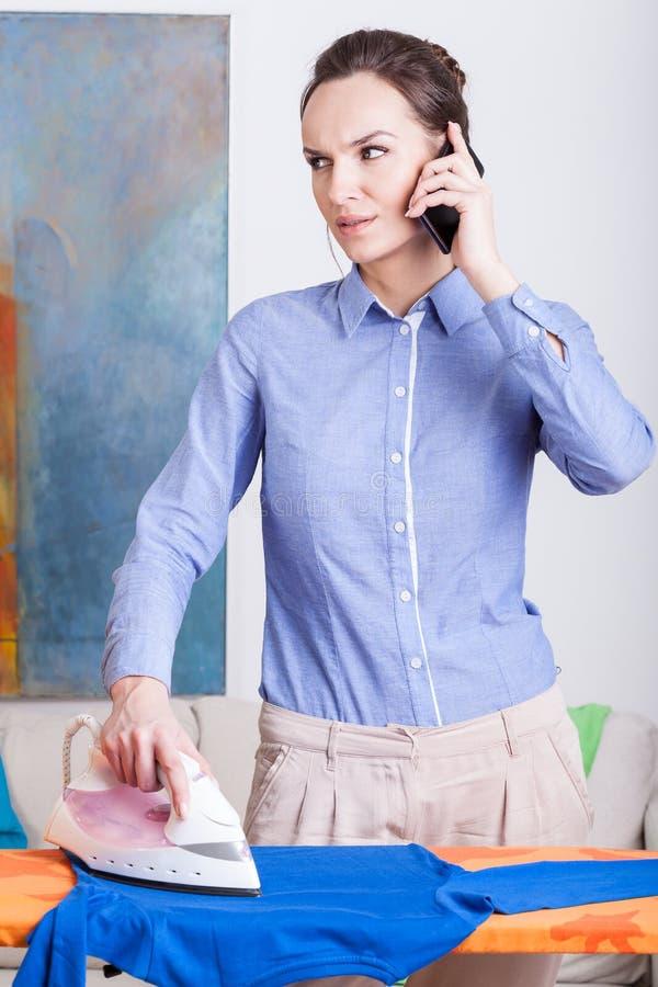 Kvinnastrykningkläder och samtal på mobiltelefonen arkivfoto