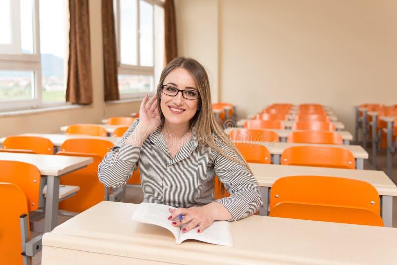 Kvinnastudent With Books Sitting i klassrum fotografering för bildbyråer