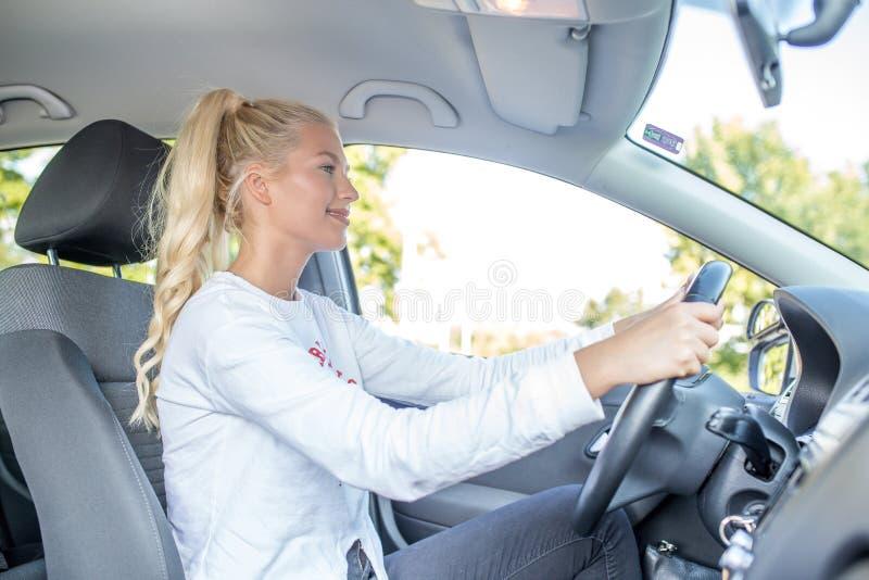 Kvinnastudent som kör en bil royaltyfria foton