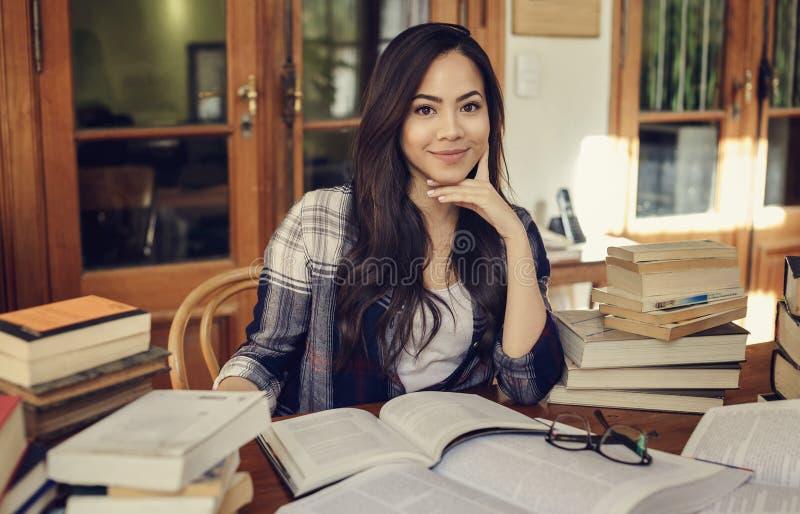 Kvinnastudent som studerar med mycket pappers- böcker arkivfoto