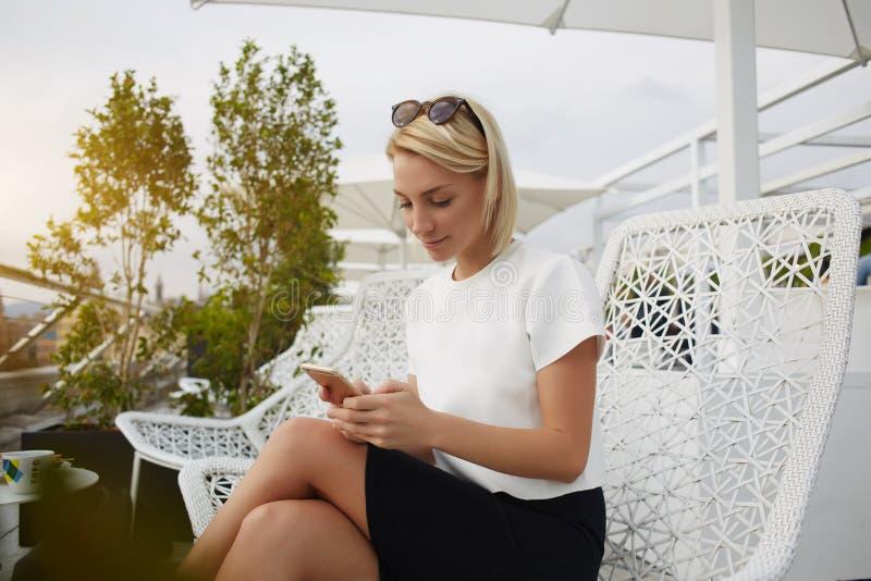 Kvinnastudenten håller ögonen på foto på mobiltelefonen, medan vilar i kafé efter föreläsningar royaltyfri fotografi