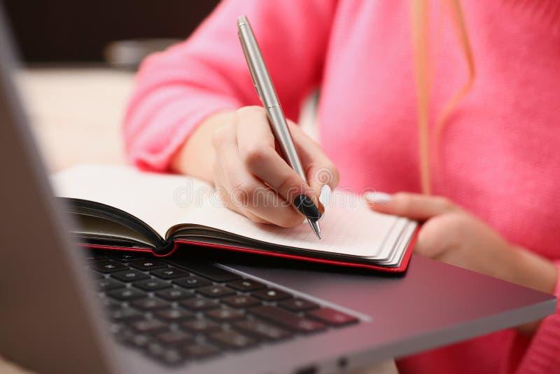 Kvinnastudien skriver hårt ner information till anteckningsboken royaltyfri foto