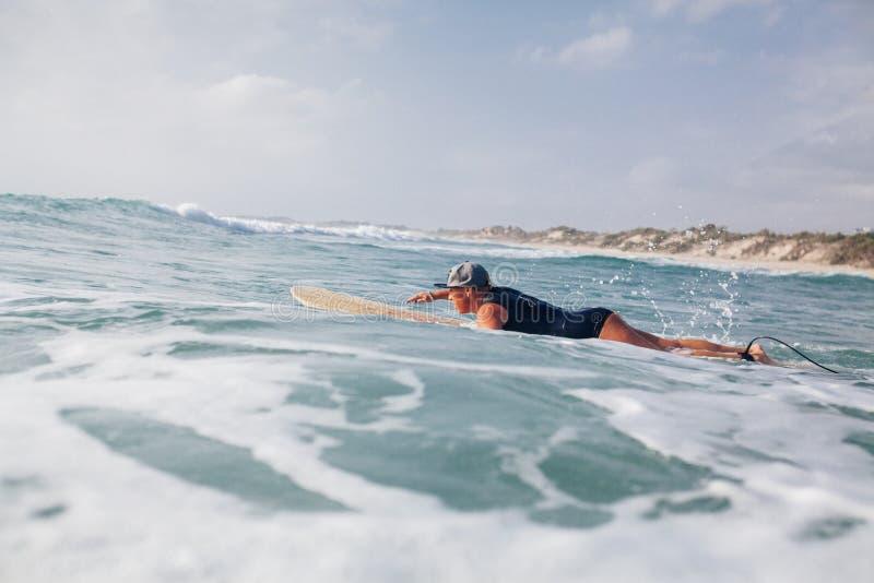 Kvinnasurfaresimning i havet royaltyfri bild