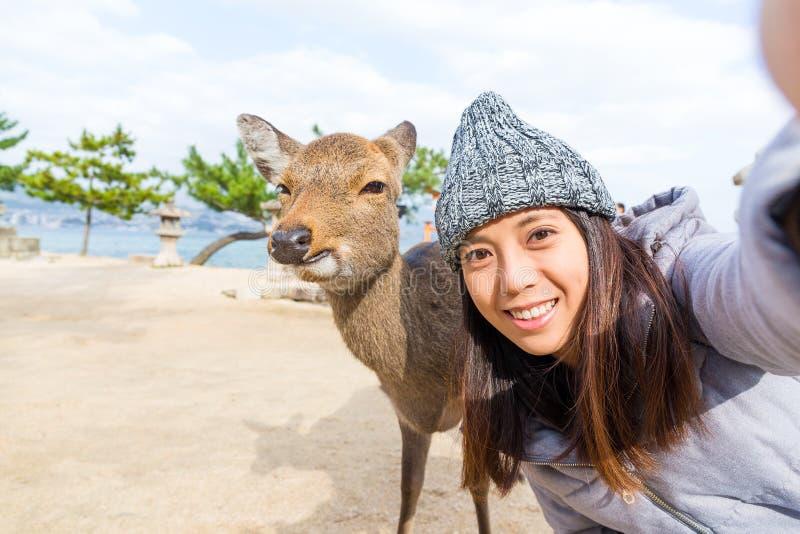 Kvinnatakignselfie med hjortar i Itsukushima fotografering för bildbyråer