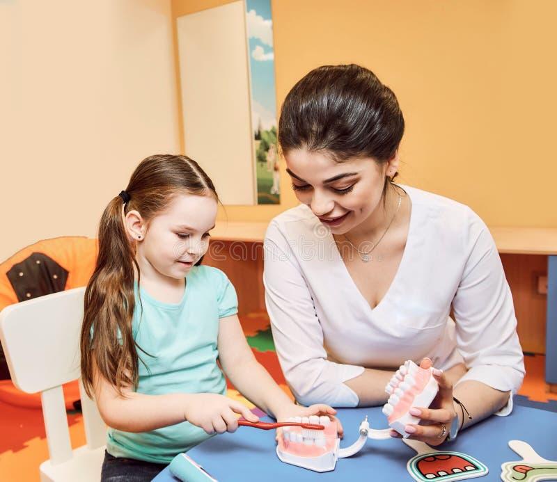 Kvinnatandläkaren undervisar lilla flickan att borsta hennes tänder royaltyfri foto