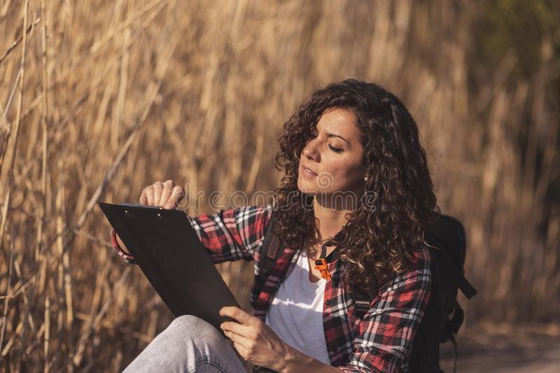 Kvinnateckning i en sketchbook utomhus royaltyfri bild