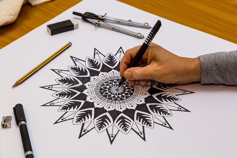 Kvinnateckning och måla en Mandala i svartvitt royaltyfri foto