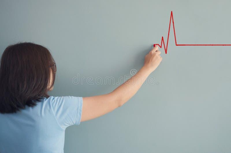 Kvinnateckningshjärtslag med röd krita på väggen royaltyfri foto