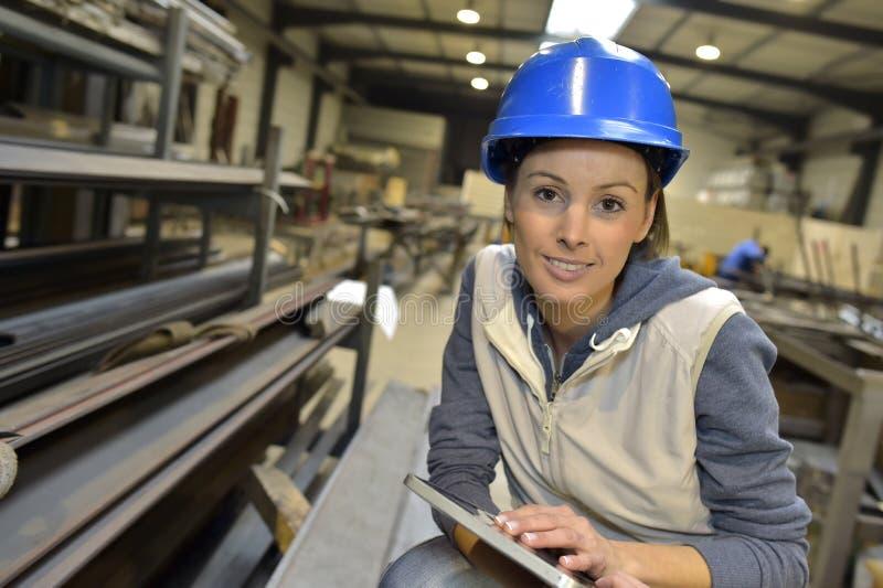 Kvinnatekniker i en metallurgisk bransch med minnestavlan arkivfoto