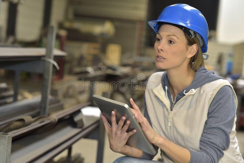 Kvinnatekniker med en säkerhetshjälm i stålväxt genom att använda minnestavlan arkivbild