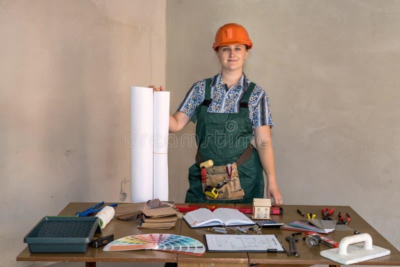 Kvinnatekniker på arbetsplatsen med ritningar arkivbild